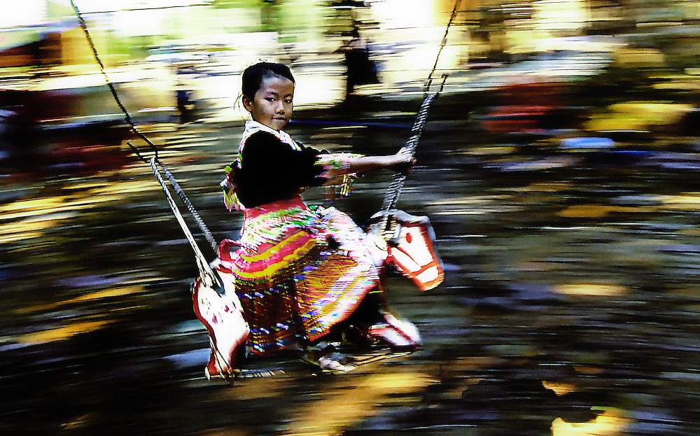 A Hmong girl during the Hmong New Year celebrations enjoys a merry go round ride.