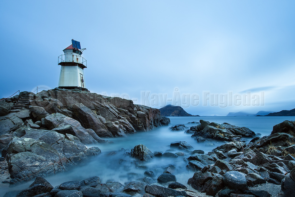 """Lighthous in the blue hour"" is taken at Golleneset, Kvalsvik, Norway. The bridge in the background is ""Rundebrua"". This picture is taken with a ""big stopper"" filter that reduces the light with 10 steps. Hence I achieved almost 4 minutes shutter time in daylight. 