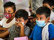 "22 JANUARY 2018 - GUINOBATAN, ALBAY, PHILIPPINES:   Students at Muladbucad Grande Elementary School in Guinobatan wear face masks in a class about volcano preparation. Several communities in Guinobatan were hit ash falls from the eruptions of the Mayon volcano and many people wore face masks to protect themselves from the ash. There were a series of eruptions on the Mayon volcano near Legazpi Monday. The eruptions started Sunday night and continued through the day. At about midday the volcano sent a plume of ash and smoke towering over Camalig, the largest municipality near the volcano. The Philippine Institute of Volcanology and Seismology (PHIVOLCS) extended the six kilometer danger zone to eight kilometers and raised the alert level from three to four. This is the first time the alert level has been at four since 2009. A level four alert means a ""Hazardous Eruption is Imminent"" and there is ""intense unrest"" in the volcano. The Mayon volcano is the most active volcano in the Philippines. Sunday and Monday's eruptions caused ash falls in several communities but there were no known injuries.  PHOTO BY JACK KURTZ"