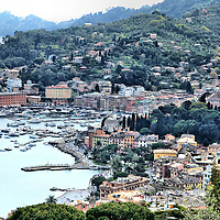 Aerial View of Seaport and Hills in Santa Margherita Ligure, Italy <br /> Santa Margherita Ligure is a picturesque town of less than 10,000 residents along the Italian Riviera neighboring Camogli, Recco and Rapallo. Although the seaport still harbors a fleet of fishing boats, you will also see plenty of yachts and pleasure boats as you stroll along the waterfront promenade. Among its historic highlights are a 13th century church and a mid-16th century castle. Santa Margherita is a charming place to stretch your legs, have a lunch or dinner of fresh fish or relax for days in its quaint splendor.
