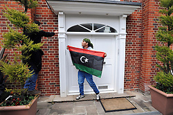 ©London News pictures. 09/03/11. Men pin the Libian opposition flag to the the door. A legal notice on the door. Squatters on the roof of a house belonging to the Gaddafi family in Hampstead today. Picture Credit should read Stephen Simpson/LNP