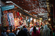 "SHOT 11/1/09 11:29:51 AM - Tourists and locals pass an endless selection of textiles in the Souk Marine in Marrakech or Marrakesh, Morocco. Marrakech is known as the ""Red City"", is an important and former imperial city in Morocco. It has a population of 1,070,838 (as of 2004), and is the capital of the mid-southwestern economic region of Marrakech-Tensift-Al Haouz, near the foothills of the snow-capped Atlas Mountains. Like many North African and Middle Eastern cities, Marrakech comprises both an old fortified city (the médina) and an adjacent modern city (called Gueliz). Marrakech has the largest traditional market (souk) in Morocco and also has one of the busiest squares in Africa and the world, Djemaa el Fna.[2] The square bustles with acrobats, story-tellers, water sellers, dancers, and musicians. By night, the square turns into food stalls, becoming a huge open-air restaurant. Morocco, officially the Kingdom of Morocco is a country located in North Africa with a population of nearly 32 million people and an area just under 173,000 squrare miles.(Photo by Marc Piscotty / © 2009)"