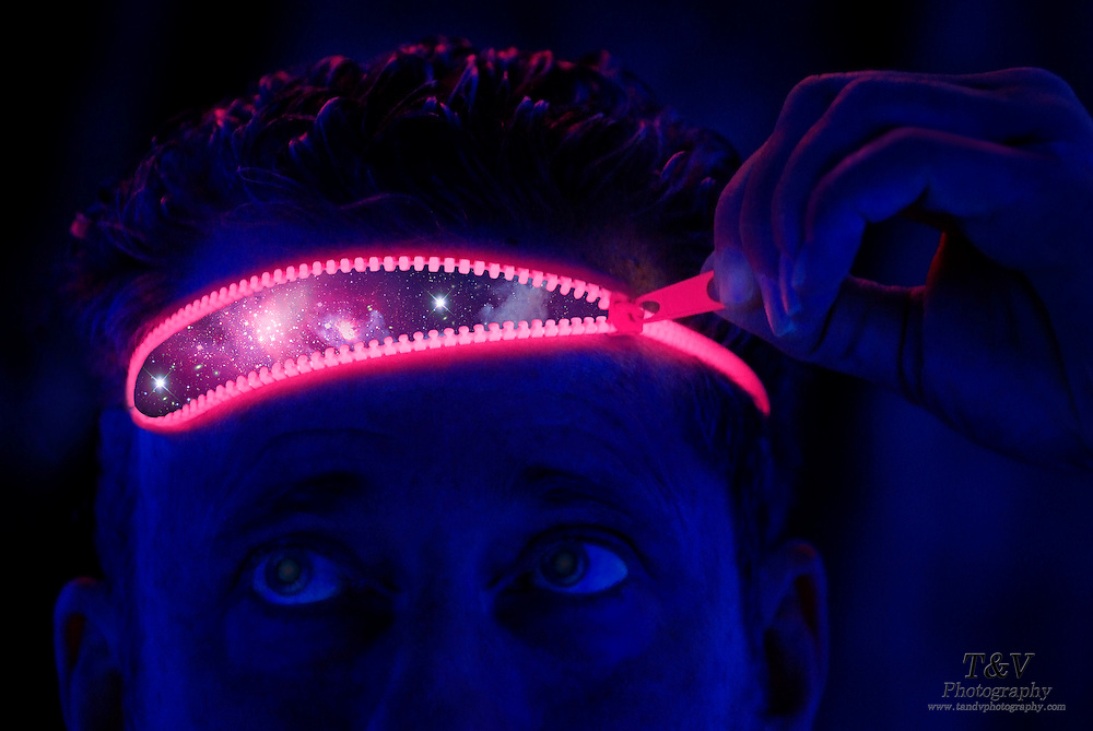 Man opens a glowing zipper on his forehead revealing a star field.Black light