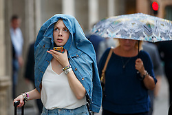 © Licensed to London News Pictures. 07/06/2016. London, UK. People taking shelter in the rain in central London on Tuesday, 7 June 2016. Photo credit: Tolga Akmen/LNP