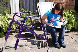 Young woman with Cerebral Palsy who uses a walking frame studying in garden.