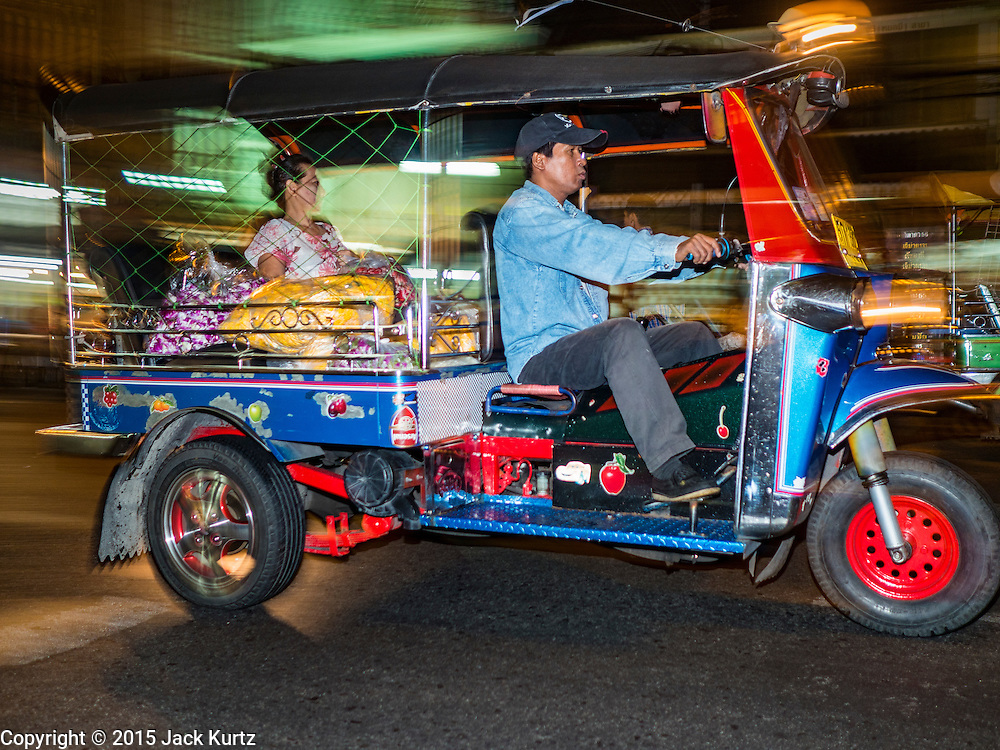 "21 DECEMBER 2015 - BANGKOK, THAILAND: A tuk-tuk, or three wheeled taxi, on the street in front of Pak Khlong Talat, also called the Flower Market. The market has been a Bangkok landmark for more than 50 years and is the largest wholesale flower market in Bangkok. A recent renovation resulted in many stalls being closed to make room for chain restaurants to attract tourists. Now Bangkok city officials are threatening to evict sidewalk vendors who line the outside of the market. Evicting the sidewalk vendors is a part of a citywide effort to ""clean up"" Bangkok.       PHOTO BY JACK KURTZ"
