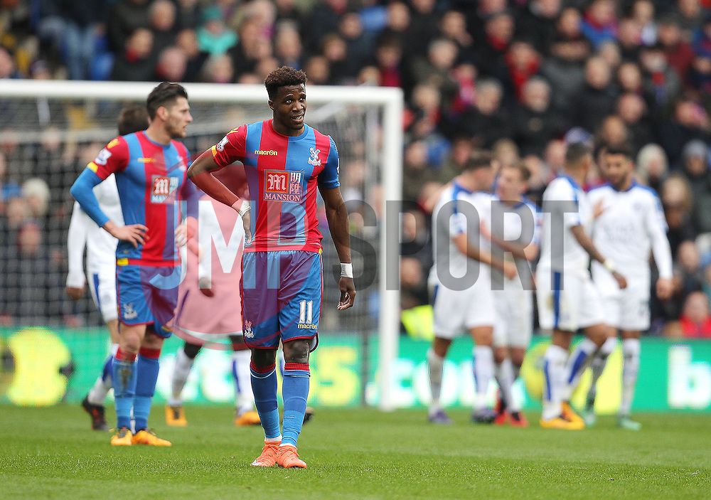 Wilfried Zaha of Crystal Palace looks dejected as the Leicester City team celebrate after scoring the opening goal - Mandatory byline: Paul Terry/JMP - 19/03/2016 - FOOTBALL - Selhurst Park - London, England - Crystal Palace v Leicester City - Barclays Premier League