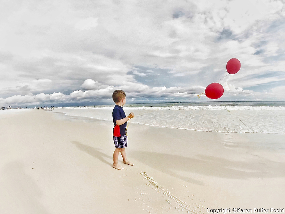 A child plays with balloons on the beach. <br /> &copy; Karen Pulfer Focht-ALL RIGHTS RESERVED-NOT FOR USE WITHOUT WRITTEN PERMISSION