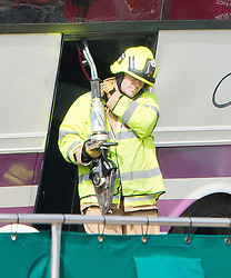 © London News Pictures. 11/09/2012. Hindhead, UK . Fire crews carrying cutting equipment at the scene of a fatal bus crash on the north bound A3 motorway near Hindhead Tunnel, Hindhead, Surrey on September 11, 2012.Three people were killed and a number of others seriously injured when a coach carrying overturned after crashing into a tree. Photo credit: Ben Cawthra/LNP