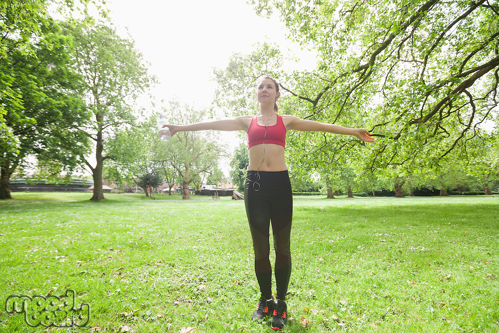 Full length of young woman listening to music while exercising in park