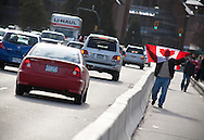 A man walks towards Downtown over Burrard Bridge, cheering and displaying a Canadian flag to vehicles driving in the other direction.<br /> <br /> Tens of thousands of people in Vancouver took to the streets on Sunday 28th February 2010 to celebrate Canada's 3-2 overtime win over the United States for the gold medal in men's Olympic hockey...Traffic came to a halt in and around the downtown of the host city for the Winter Games following the dramatic finish to the match, which featured Sidney Crosby scoring to secure the victory on the final day of Olympic competition.
