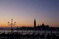 Gondolas at sunrise and Basilica San Giorgio Maggiore in silhouette in the background;<br /> Venice, Italy
