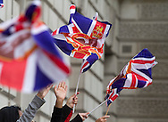 A crowd of onlookers waving Union flags in Whitehall, London, as the newly-wed Prince William and Catherine Middleton drive from the marriage ceremony towards Buckingham palace. The wedding was held at Westminster Abbey. Tens of thousands of people lined the streets to wish the couple well before and after the ceremony.