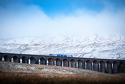 © Licensed to London News Pictures. 25/11/2017. Gearstones UK. The 07:30 train from Ribblehead to Carlisle crosses the Ribblehead viaduct this morning in the shadow of Whernside mountain after a night of snow fall in the Yorkshire Dales. Photo credit: Andrew McCaren/LNP