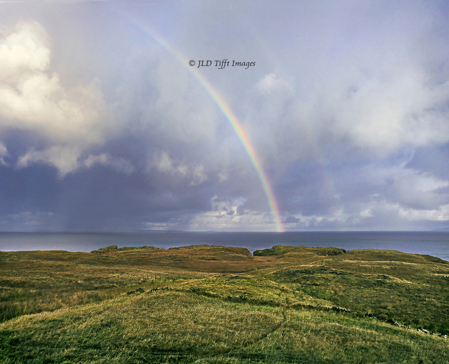 Double rainbow over the North Sea seen from the north coast of the Isle of Mull, Western Isles, Scotland.  In the foreground, moorland cris crossed with narrow dirt paths.  Overhead a dramatically cloudy sky.