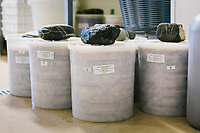 """PISCIOTTA, ITALY - 22 APRIL 2018: Salted alici di Menaica (Menaica anchovies) are packed in PVC containers in the processing workshop of """"Alici di Menaica"""", owned by the Donatella Marino and her husband Vittorio Rimbaldo, in Pisciotta, Italy, on April 22nd 2018.<br /> <br /> Former restaurant owners Donatella Marino and her husband Vittorio Rimbaldo have spent the recent years preparing and selling salted anchovies, called alici di menaica, to a growing market thanks to a boost in visibility from the non-profit Slow Food.  The ancient Menaica technique is named after the nets they use brought by the Greeks wherever they settled in the Mediterranean. Their process epitomizes the concept of slow food, and involves a nightly excursion with the special, loose nets that are built to catch only the larger swimmers. The fresh, red anchovies are immediately cleaned and brined seaside, then placed in terracotta pots in between layers of salt, to rest for three months before they're aged to perfection.While modern law requires them to use PVC containers for preserving, the government recently granted them permission to use up to 10 chestnut wood barrels for salting in the traditional manner. The barrels are """"washed"""" in the sea for 2-3 days before they're packed with anchovies and sea salt and set aside to cure for 90 days. The alici are then sold in round terracotta containers, evoking the traditional vessels that families once used to preserve their personal supply.<br /> <br /> Unlike conventional nets with holes of about one centimeter, the menaica, with holes of about one and half centimeters, lets smaller anchovies easily swim through. The point may be to concentrate on bigger specimens, but the net also prevents overfishing."""