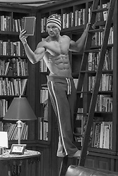 sexy shirtless man at home in a library