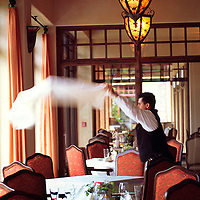 A waiter throws a tablecloth over a dining table at a Country Club's restuarant