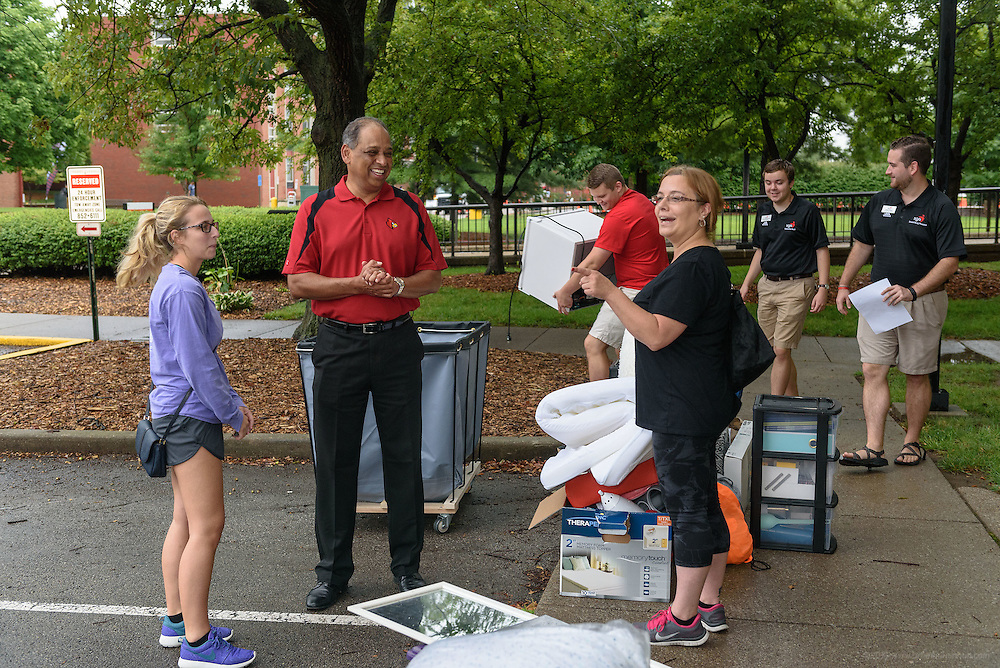 Freshman Bailey Thompson, 18, left, listens as University of Louisville Acting President, Dr. Neville Pinto, center, talks with her mother, Jennifer Burden, while volunteers put her belongings into a cart as first-time students move in to Belknap Campus dormitories Wednesday during U of L's Welcome Week. Aug. 17, 2016