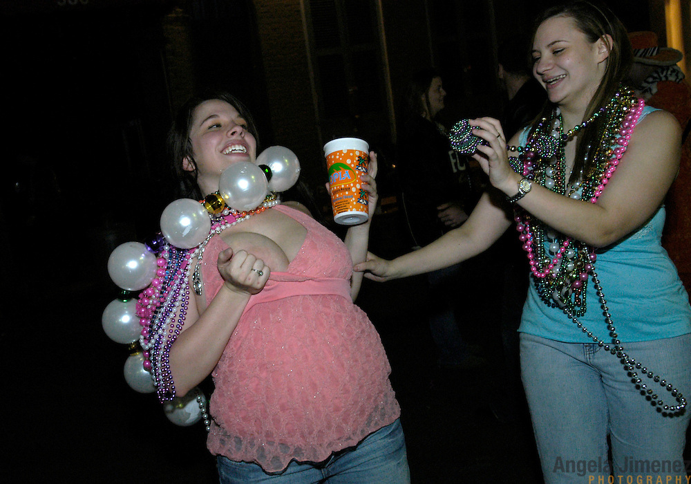 Revelers celebrate the first Mardi Gras since Hurricane Katrina ravaged the city on Bourbon Street in New Orleans, Louisiana on February 23, 2006. A partier shows her breasts to people on a balcony above in exchange for Mardi Gras beads.