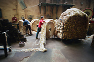 A worker rolling a circular bale of jute at Tay Spinners mill in Dundee, Scotland. This factory was the last jute spinning mill in Europe when it closed for the final time in 1998. The city of Dundee had been famous throughout history for the three 'Js' - jute, jam and journalism.