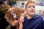 """Oct. 24, 2009 - SCOTTSDALE, AZ:  CLY HERNLY-BROWN, RN, gives the H1N1 vaccination to MATTHEW BASS, 10, from Maricopa, AZ, at Scottsdale Healthcare's Community Health Services clinic Saturday morning. The Bass family left their home in Maricopa, about 60 miles south of Phoenix, at 2:30AM to get to the clinic. The first publicly administered H1N1 (""""swine flu"""") vaccinations were given in the Phoenix area Saturday. About 52,000 doses of the vaccine, in both injection and nasal spray form, were available on a first come first served basis, but only to those in so called """"high risk"""" groups: pregnant women, children 6 months to 4 years old, children 5 years to 18 years with underlying health concerns and direct caregivers of infants less than 6 months old. More than 700 people lined up at Scottsdale Health Care, which had 500 doses of the vaccine to administer.     Photo by Jack Kurtz"""