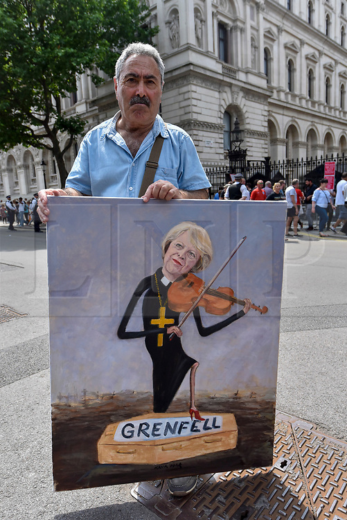 © Licensed to London News Pictures. 17/06/2017. London, UK. Satirical artist Kaya Mar and his latest painting.  Demonstrators gather outside Downing Street to protest against Theresa May following the results of the General Election, the Conservatives' proposed coalition with the DUP and the Grenfell Tower fire tragedy. Photo credit : Stephen Chung/LNP