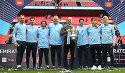 Manchester City manager Pep Guardiola (centre) celebrates with the trophy after winning the FA Cup Final with coaching staff (left to right) Richard Wright, Xabi Mancisidor, Lorenzo Buenaventura, Rodolfo Borrell, Mikel Arteta, Carles Planchart and Brian Kidd during the FA Cup Final at Wembley Stadium, London.