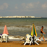 Early in the morning, Ali cleans the beach front and prepares the tables for the customers. On the back the island of Arwad, Tartus, Syria. Tôt le matin, Ali nettoie son coin de plage et prépare l'arrivée des clients. A l'arrière plan, l'ile d'Arwad, Syrie.