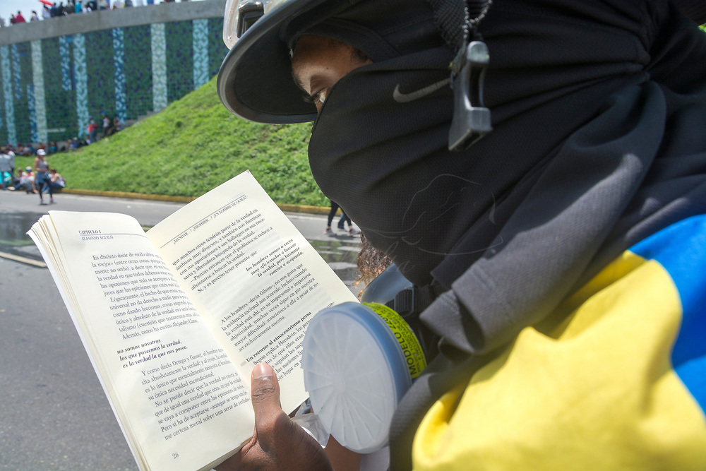 "Un joven con una máscara anti-gas, lee un libro llamado ""Tolerancia"" en la protesta llamada el Gran Plantón. Los ciudadanos venezolanos, opuestos al gobierno de Nicolás Maduro, se quedaron 12 horas en el Gran Plantaón del distribuidor Altamira, en la carretera Francisco Fajardo. 15 de mayo de 2017. A young man with an anti-gas mask, reads a book called ""Tolerance"" in the protest called the Great Planton. Venezuelan citizens, opposed to the government of Nicolas Maduro, stayed for 12 hours in the ""Gran Plantón"" of the distributor Altamira, on the highway Francisco Fajardo. May, 15, 2017"