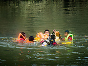 20 SEPTEMBER 2015 - SARIKA, NAKHON NAYOK, THAILAND:  Swimmers guide the Ganesha deity downriver at the Ganesh festival at Shri Utthayan Ganesha Temple in Sarika, Nakhon Nayok. Ganesh Chaturthi, also known as Vinayaka Chaturthi, is a Hindu festival dedicated to Lord Ganesh. Ganesh is the patron of arts and sciences, the deity of intellect and wisdom -- identified by his elephant head. The holiday is celebrated for 10 days. Wat Utthaya Ganesh in Nakhon Nayok province, is a Buddhist temple that venerates Ganesh, who is popular with Thai Buddhists. The temple draws both Buddhists and Hindus and celebrates the Ganesh holiday a week ahead of most other places.   PHOTO BY JACK KURTZ