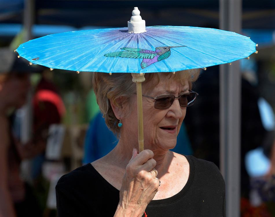 "gbs073017n/ASEC -- Kris Mathieson of Rio Rancho shades herself from the sun with an oriental parasol made by her daughter at the Corrales Growers Market on Sunday, July 30, 2017. Mathieson's daughter, JoAnne Blackstone had a booth in the Makers Market. Her business, ""Pawsabilities,"" shares the profits from the sales of her parasols with the Human Society.(Greg Sorber/Albuquerque Journal)"