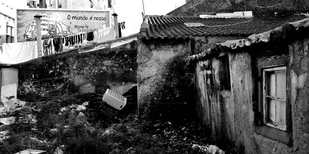 Lisbon, Portugal - <br /> An abandoned house in Campo de Ourique, and old part of Lisbon, near Amoreiras Shopping Center, one of the first and major Shopping Center build in Lisbon. On the board on the back is &quot;The World Is Ours. Dare To Discover&quot;. This photo is part of an one week reportage on Portuguese Daily Life, between Dec 17 and Dec 21, 2012, on the year that the austerity measures set by the Portuguese Government to achieve the goals set by the Troika (IMF, ECB, EC) for the Portuguese Bailout Package, result in the highest unemployment rates ever since the beginning of Portuguese Democracy (1974) and poverty starts to show on the former middle class families.<br /> Photo Credit: Pedro Nunes/4SEE