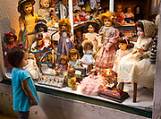 Young girl admires antique dolls in shop window, Buenos Aires, Argentina.