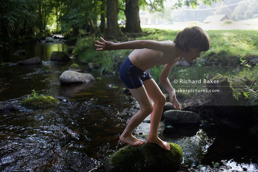 Archive image - also used in the book 'Risk Wise'.<br /> <br /> Wearing his bathing costume, a young adventurer clambers over rocks in the Gross Enz river in Germany's Black Forest. The lad of 10 crouches to better balance himself, carefully placing his bare feet on the slippery rock's surface as he emerges from the chilly mountain water. It is high summer and we can see the boy backlit by the glare of strong sunlight in the background. The Gross Enz river rises in Enzklosterle in Baden-Württemberg and is an eventual  tributary of the Neckar. Geologically, the Black Forest consists of a cover of sandstone on top of a core of gneiss. During the last glacial period, the Würm glaciation, the Black Forest was covered by glaciers.