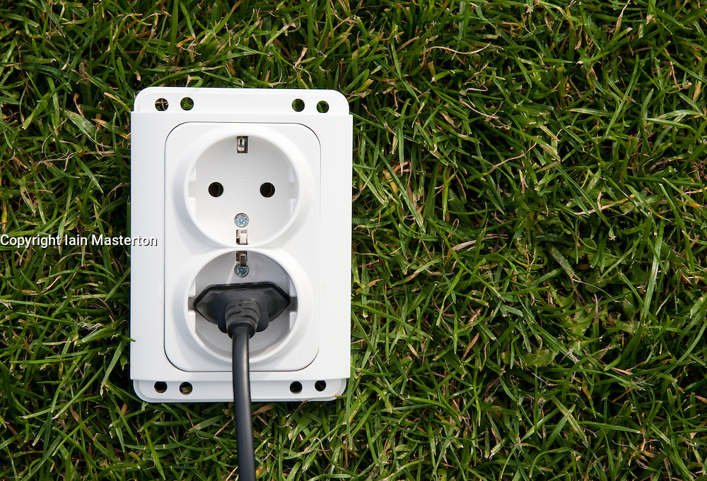 Electric socket and plug on grass illustrating concept of green or clean electric power