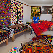 Teotitlán del Valle is a small village part of the Tlacolula Valley district. It is known for its textiles, especially rugs, which are woven on hand-operated looms, from wool obtained from local sheep and dyed mainly with local, natural dyes. They combine historical Zapotec designs with contemporary designs such as reproductions of famous artists' work