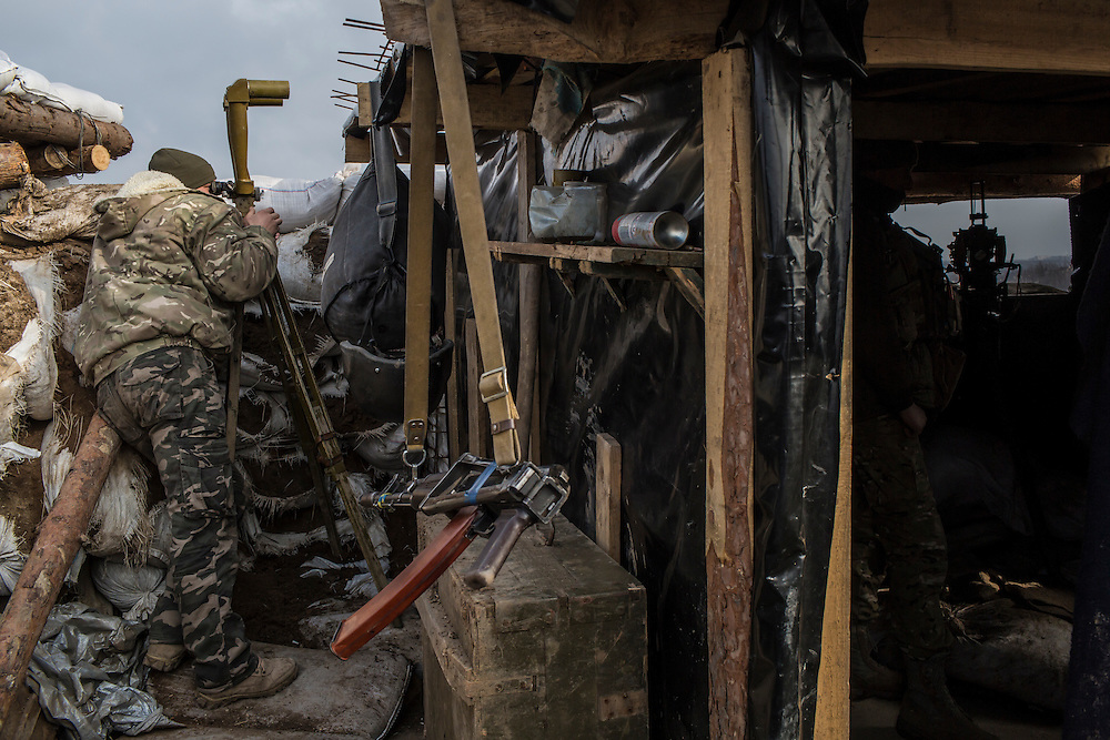 MARIINKA, UKRAINE - FEBRUARY 21, 2016: A soldier from the 1st Mechanized Battalion, 14th Mechanized Brigade of the Ukrainian Army looks toward territory held by pro-Russian rebels from a front-line position in Mariinka, Ukraine. The Donetsk suburb has been the scene of some of the heaviest fighting recently between Ukrainian forces and pro-Russian rebels. CREDIT: Brendan Hoffman for The New York Times