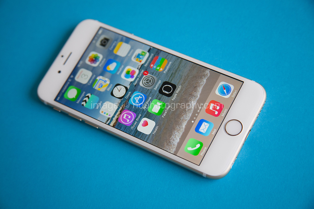 Gold and white Apple iPhone 6 against a blue background