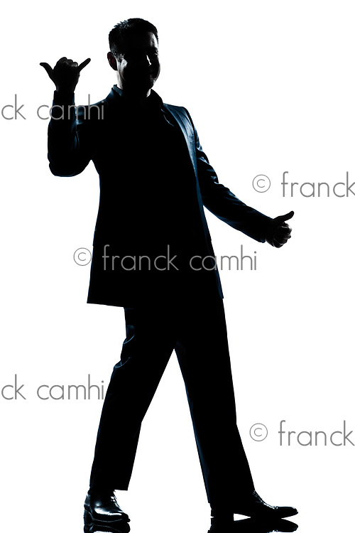 one caucasian man happy saluting shaka sign full length silhouette in studio isolated white background