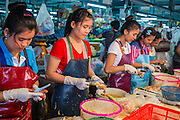 "03 OCTOBER 2012 - BANGKOK, THAILAND:   Women process seafood for sale in Khlong Toey Market in Bangkok. Khlong Toey (also called Khlong Toei) Market is one of the largest ""wet markets"" in Thailand. Thousands of people shop in the sprawling market for fresh fruits and vegetables as well meat, fish and poultry every day.     PHOTO BY JACK KURTZ"