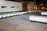 With the dock doors full of trailers, a newspaper printing warehouse is preparing for the morning run.