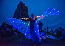 © Licensed to London News Pictures; 20/06/2020; Glastonbury, Somerset, UK. A woman wears an illuminated cape as people gather on Glastonbury Tor for sunset on the Summer Solstice weekend on the longest day of the year today at midsummer. This year due to the coronavirus Covid-19 pandemic and concerns over social distancing at gatherings of people, Stonehenge and Avebury where thousands of people usually gather to celebrate the summer solstice are closed to the public, with the solstice live streamed from Stonehenge. Glastonbury authorities had also asked people to refrain from coming to Glastonbury for the solstice but hundreds came with many staying the night on the Tor. Glastonbury Tor is a hill outside Glastonbury town, topped by the roofless St Michael's Tower, a Grade I listed building which is what remains of the Church of St Michael built in the 14th century. The entire site is managed by the National Trust and has been designated a scheduled monument. Photo credit: Simon Chapman/LNP.