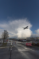 Heathrow Airport, London, March 28th 2016. Against the backdrop of a departing storm cloud, a remnant of Storm Katie, and Airbus A320 is about to land at London Heathrow.