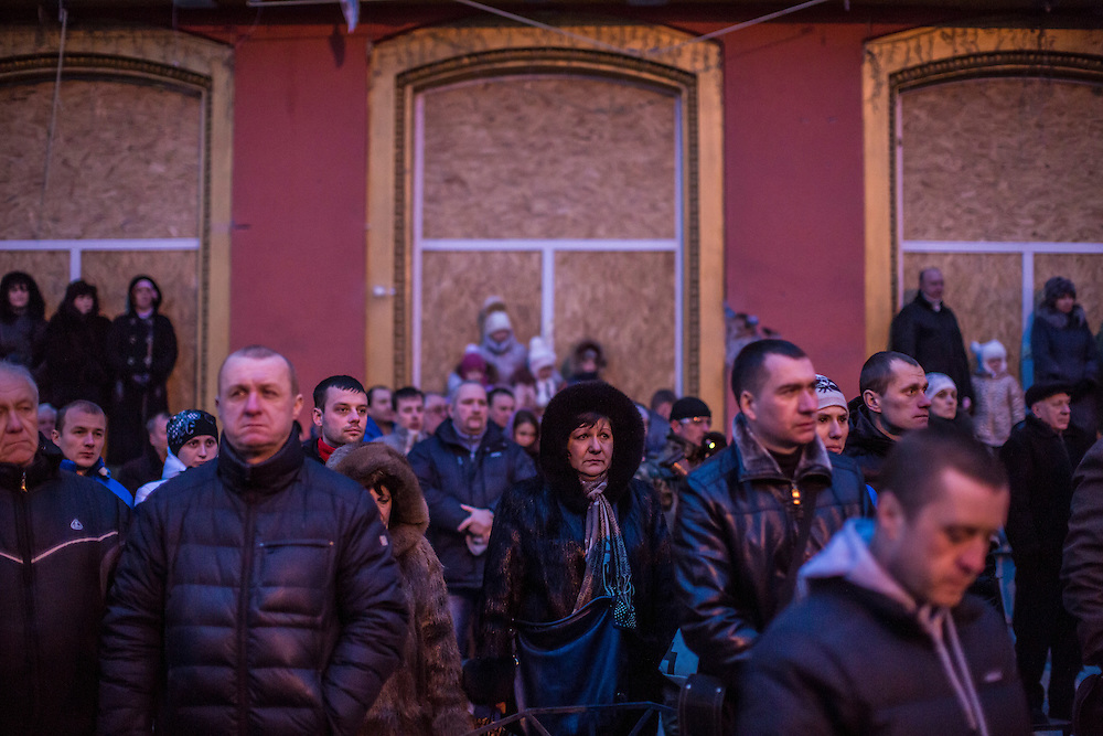 DONETSK, UKRAINE - JANUARY 24, 2015: People stand in freezing temperatures during a memorial event for victims of a rocket strike that hit a trolleybus two days earlier in Donetsk, Ukraine. The attack killed at least eight civilians and injured many more. CREDIT: Brendan Hoffman for The New York Times