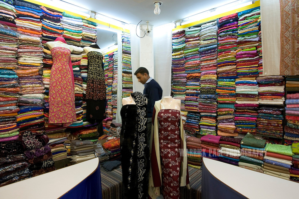 """MIRPUR, PAKISTAN - NOVEMBER 20: A tailor sorts fabrics in a woman's clothing store in Mirpur's Azad Mega Mart, November 20, 2006, Mirpur, Pakistan. Mirpur is also known as """"Little Britain"""" as its population is made predominantly of British-born Pakistani expatriates who have constructed large housing estates and British-style businesses throughout the district. Local residents claim the town has become a tax write-off for Brits with dual nationality who purchase property and housing to avoid paying taxes in England and split their time between Pakistan and the UK. (Photo by Warrick Page)"""