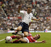 Photo: Aidan Ellis.<br />England v Austria. World Cup Qualifier. 08/10/2005.<br /><br />Luke Young finds himself tackled by Andreas Ivanschitz.