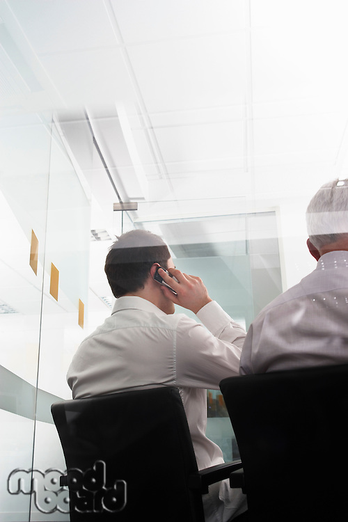Businessmen one using mobile phone sitting in office behind glass wall back view