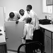 International Rescue Committee case worker Mirza Kevric shows Erick  Hakizimana and his family, for the first time,  how to use the refrigerator at their apartment.