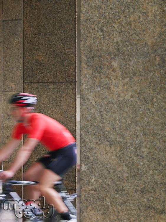 Man cycling between pillars motion blur
